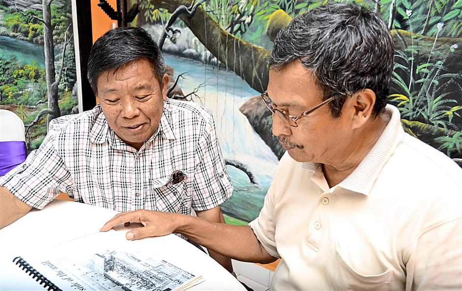 Ex-officers Md. Sabri Ismail (right) and Zainul Mustaffa reminiscing on the days they were working in Pudu Prison. while looking through the newspaper cutting.