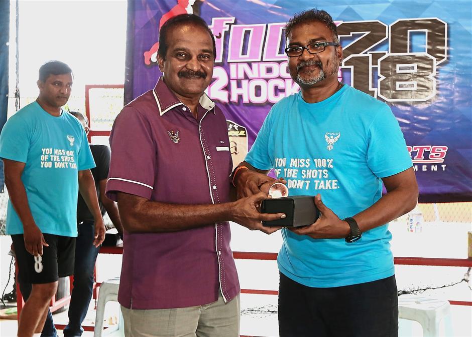 Sivasubramaniam (left) receiving a token of appreciation from tournament organiser C. Patmananthan.