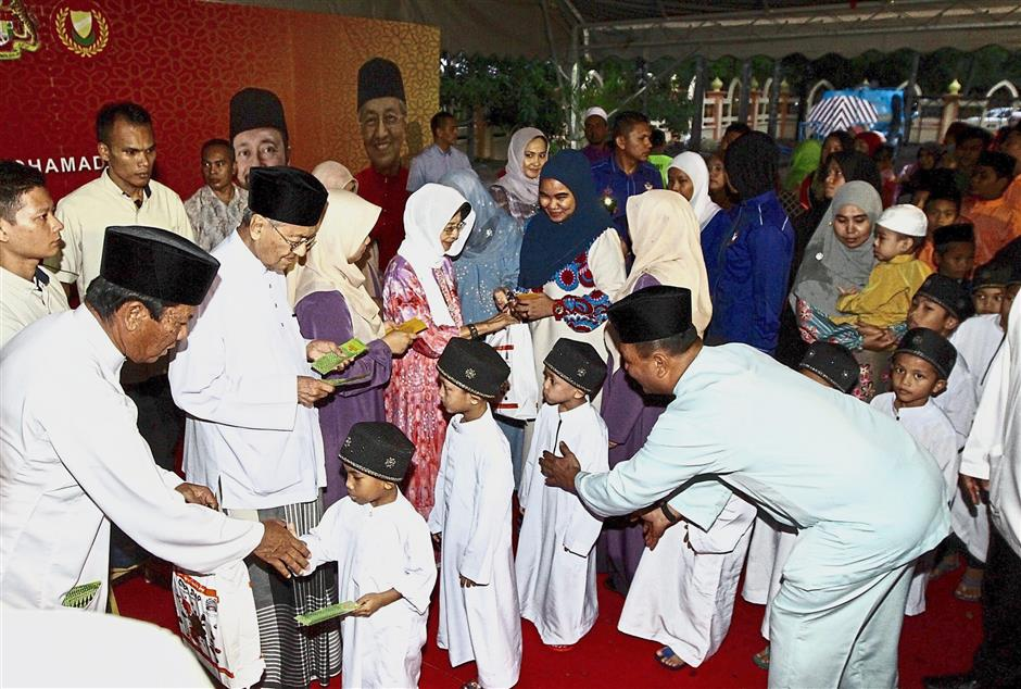 Dr Mahathir (front row, second left) and Dr Siti Hasmah (in red) handing out Raya aid to children at the Al-Hana mosque in Kuah, Langkawi. — Photos: LIM BENG TATT/The Star
