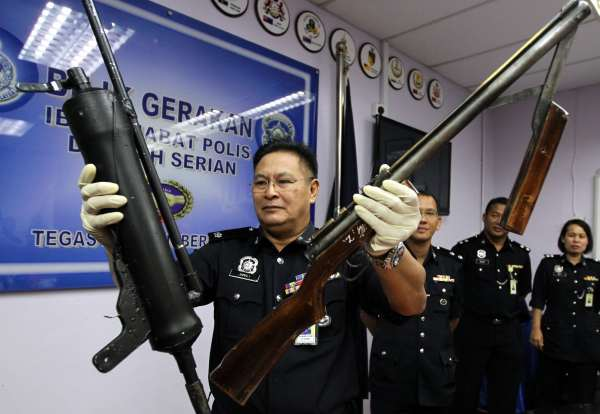 Dangerous items: Serian police chief DSP Mohd Jamali Umi showing a homemade gun (left) and an air rifle confiscated during the raid, at the press conference in Serian. u2014 ZULAZHAR SHEBLEE / The Star