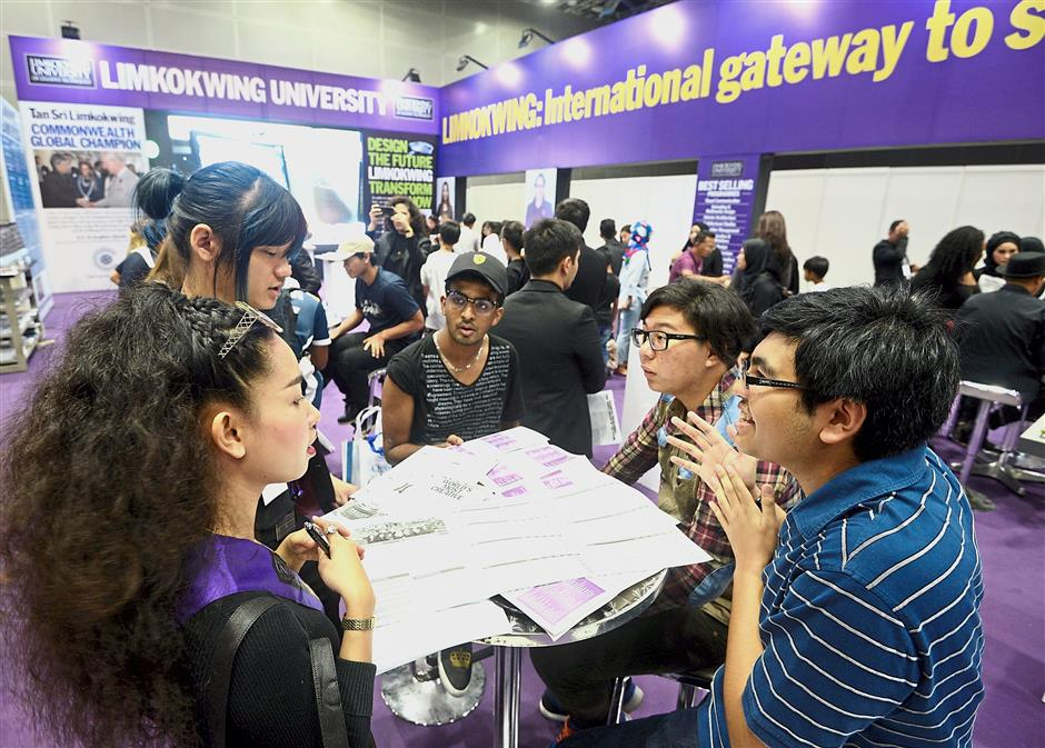 Visitors crowding around the Limkokwing University of Creative Technology booth ask about the courses offered.