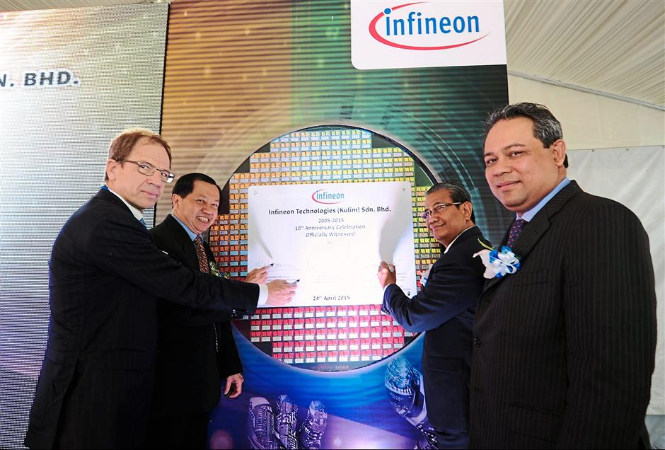 Marking a milestone: (Above from left) Dr Reinhard, Tan, Ku Rahman and Azman signing the plaque during the launch of Infineon's 10th anniversary celebration at the company plant in Kulim Hi-Tech Park. (Left pic) Wong mesmerising the audience with her sand-painting performance.