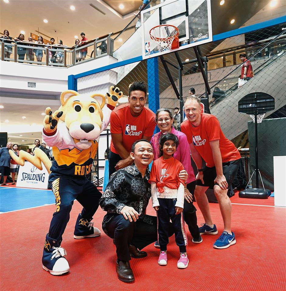 Maszlee (front, in black) made an appearance at the NBA Cares event.