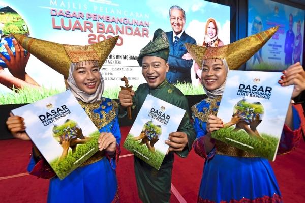 One for the album: Ministry of Rural Development staff Mohd Taufek Mohd Noh (centre) with Dhia Qaarina M. Rosli (left) and Siti Farihah Mahadzir showing the 2030 Rural Development Policy released by Dr Mahathir at the Putrajaya International Convention Centre. u2014 Bernama