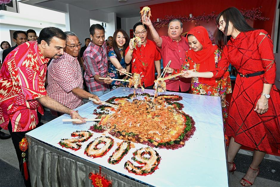 All together now: Sultan Ibrahim and Raja Zarith Sofiah tossing yee sang with Puah (fourth from right) and Cheng (right) at Puah's open house in Senibong Cove. — Bernama