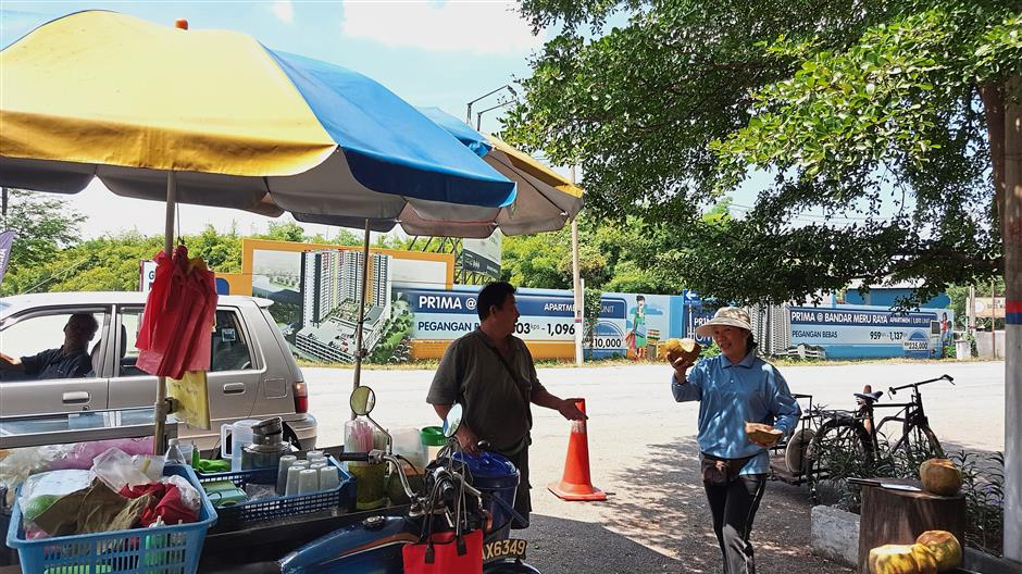Husband-wife-team Liew (left) and Lai have been running? a ?drinks and fruit stall opposite Falim House for 22 years.