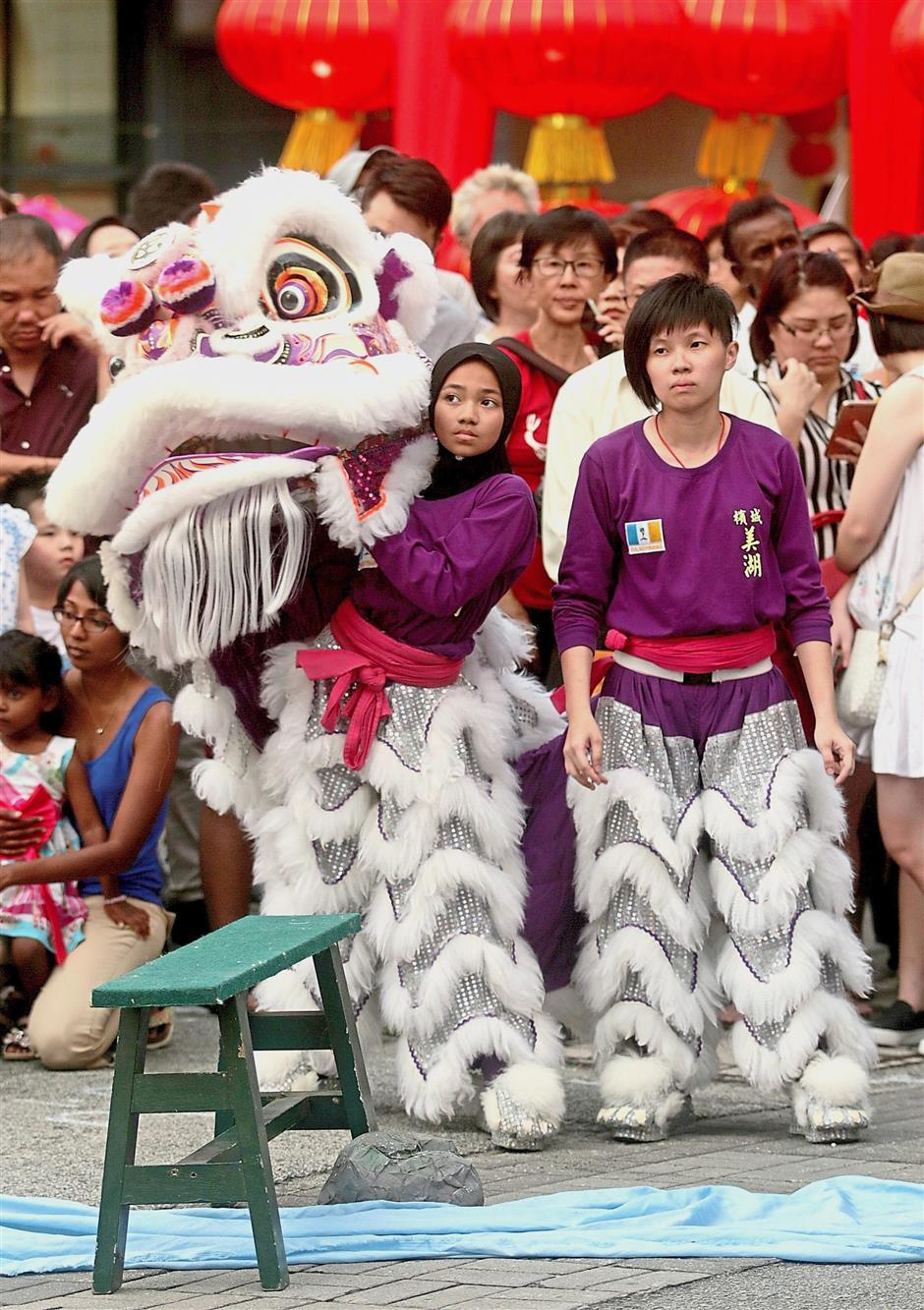 Siti Aishah and her partner Foong Kee waiting for their turn to perform the lion dance.