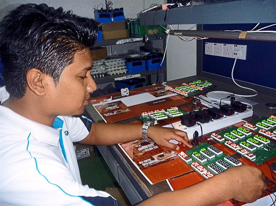 A worker testing the panel of the Islamic clock that DES is designing.