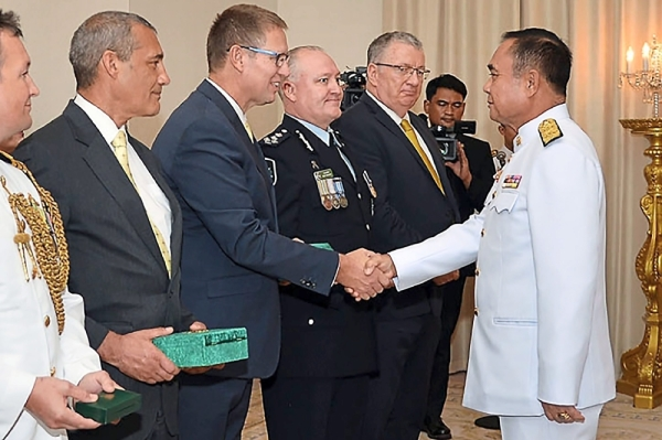 Well done: Prayut (right) shaking hands with Harris as Challen (second from left) looks on in Bangkok. u2014 AFP