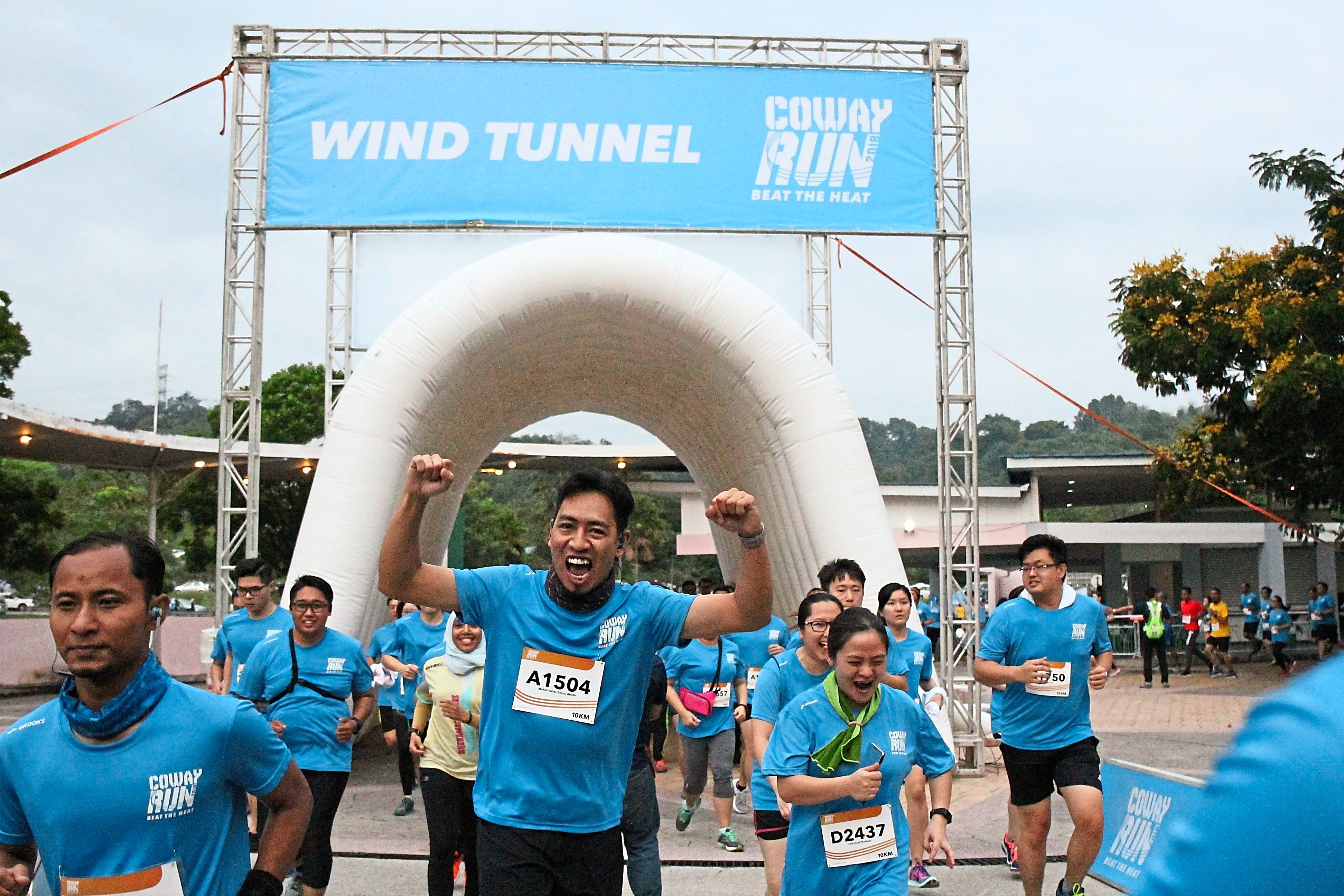 A participant all pumped up after passing under a cooling wind tunnel at the Coway Run 2018 held at Serdang.