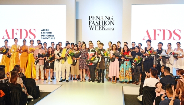 Hunza Group executive director Khor Tze Ming (front row, sixth left) Asean Fashion Designers showcase founder Hayden Ng (seventh left) and participating designers and models posing together for the cameras after the show that was part of the Penang Fashion Week 2019 in Gurney Paragon Mall.