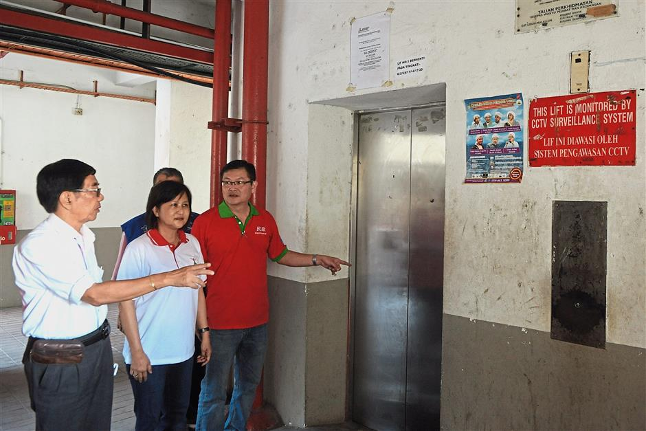(From right) H'ng, Ng and Tay checking out the lifts that are out of service at the Kedah Road flats in George Town, Penang.