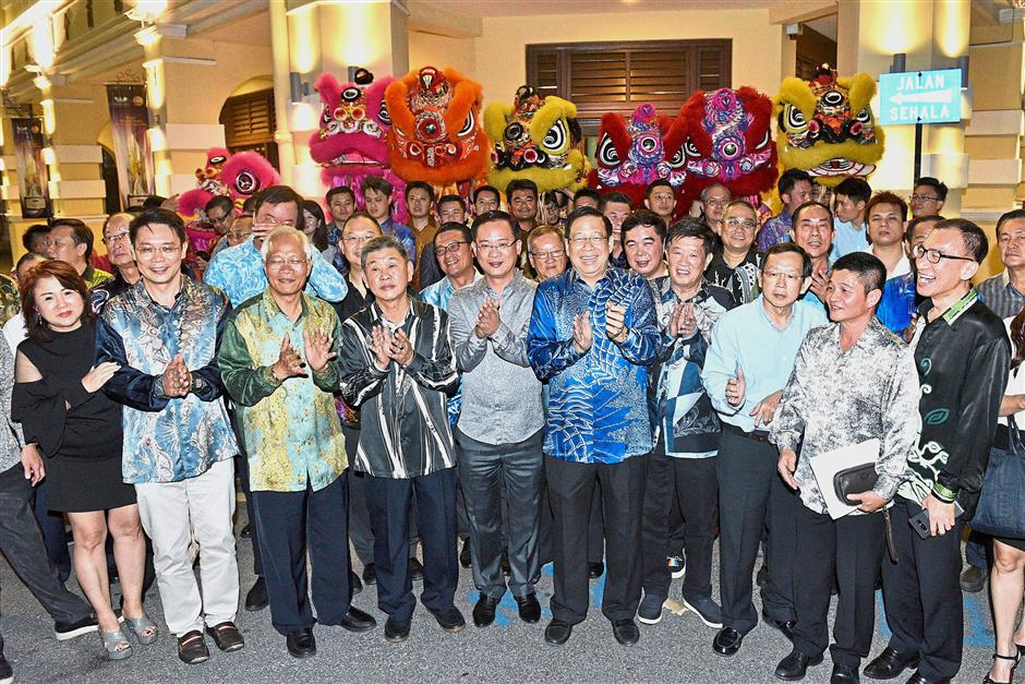 Choot (blue batik, centre) and PCCC members posing for a photograph outside the building during the celebration.