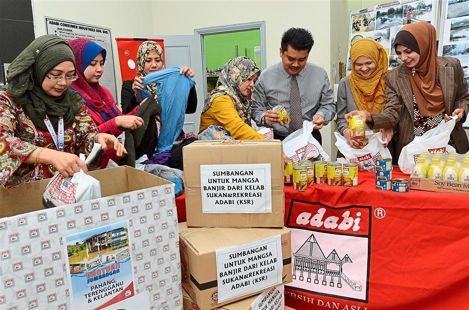 Because they care: Adrian (wearing tie) and Adabi staff packing care packages to be sent to flood victims in Kelantan.
