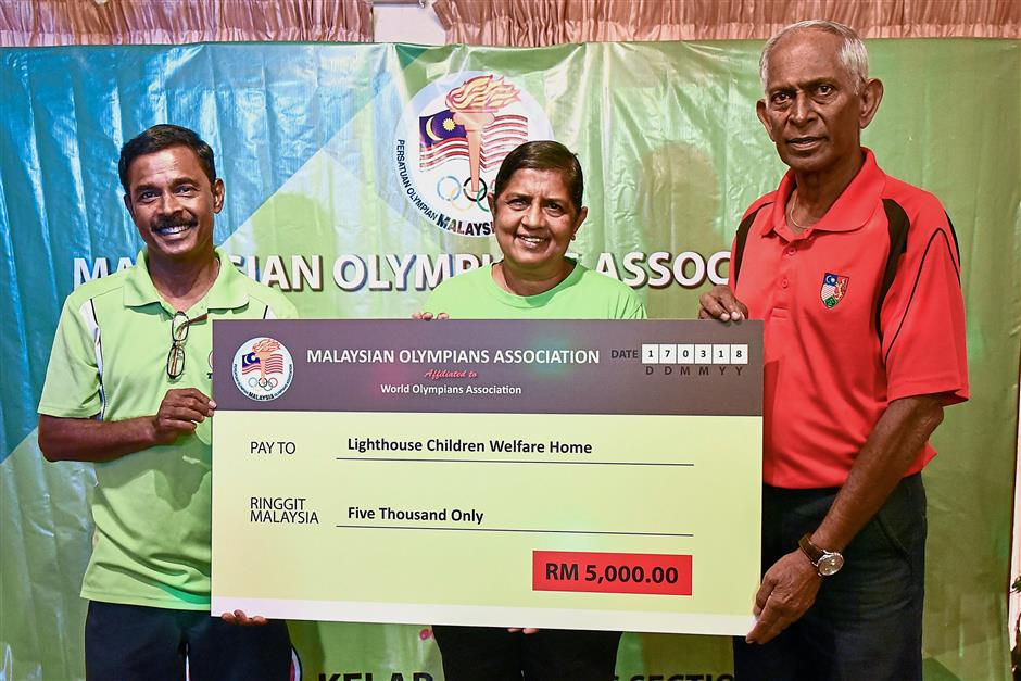 (From left) Steven and Jacinta receiving a RM5,000 mock cheque from Karu at the event.