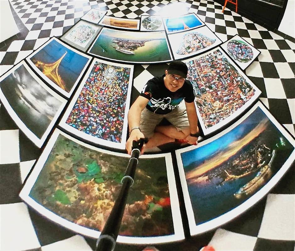 Loh taking a creative selfie while being surrounded by pictures of Penang for the exhibition.
