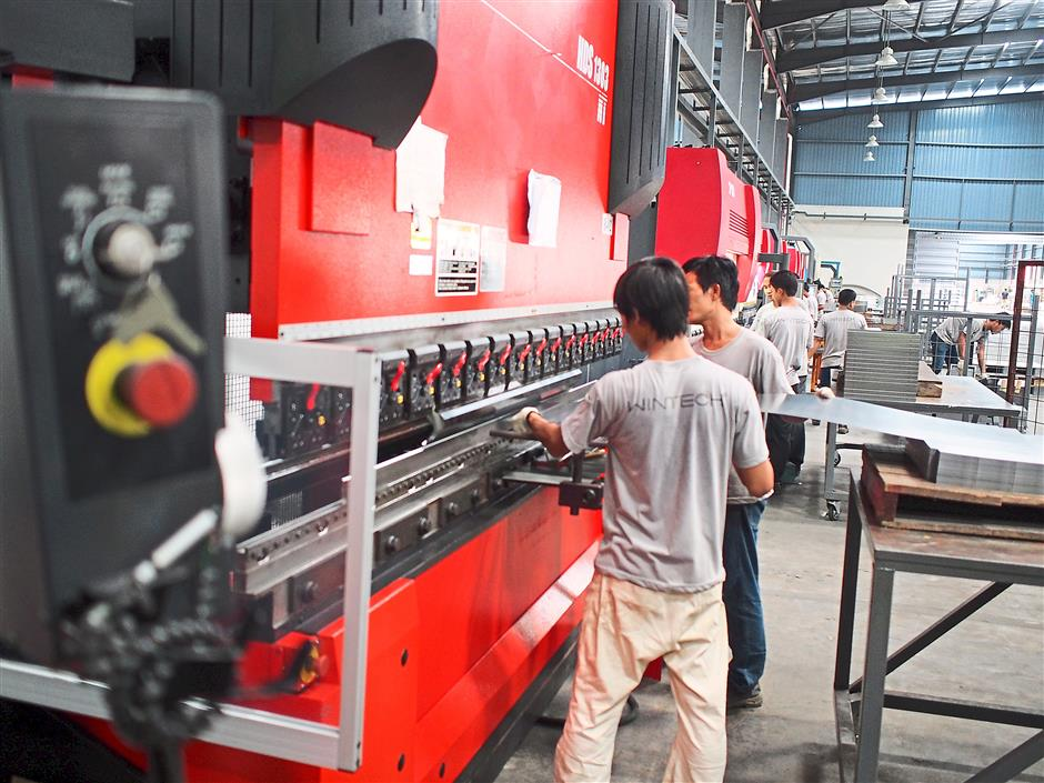 Precise cutting machine: Workers using state-of-the-art machines necessary for the production of metal cabinets.