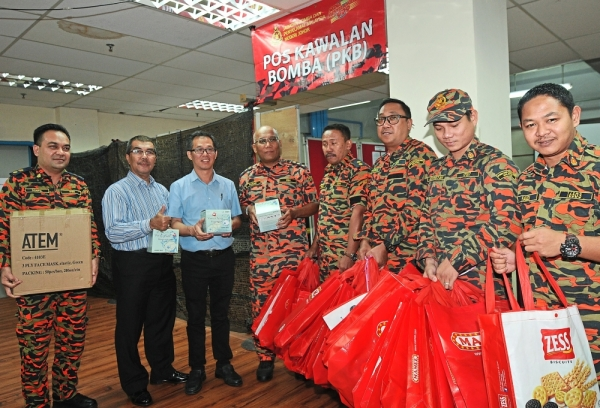 Malacca Health and Anti Drug state executive councillor Low Chee Leong (third from left) presentring masts and goodie bags to rescue personnel involved in the Pasir Gudang chemical pollution incident. With him is Johor Fire and Rescue Department director Datuk Yahya Madis (second left) and his deputy Pauzan Ahmad ((firth from left)