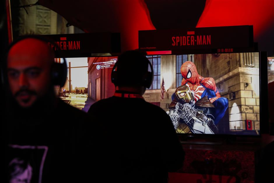 An attendee plays the Spider-Man video game during the Sony Corp. Playstation event ahead of the E3 Electronic Entertainment Expo in Los Angeles, California, U.S., on Monday, June 11, 2018. Sony corralled attendees through different venues as they put their new titles on display, including a remastered version of cult favorite Resident Evil 2 and their event finale Spider-Man. Photographer: Patrick T. Fallon/Bloomberg
