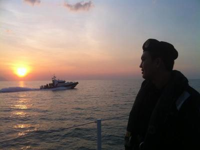 Scenic: An enforcement officer looking into the sunset as another patrol boat zips by.