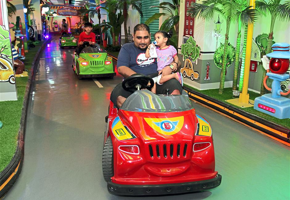 Hot ride: Red FM's The Really Really Late Breakfast Show host Kavin Jay in one of the rides at the Fun Drive zone with his daughter in hand.