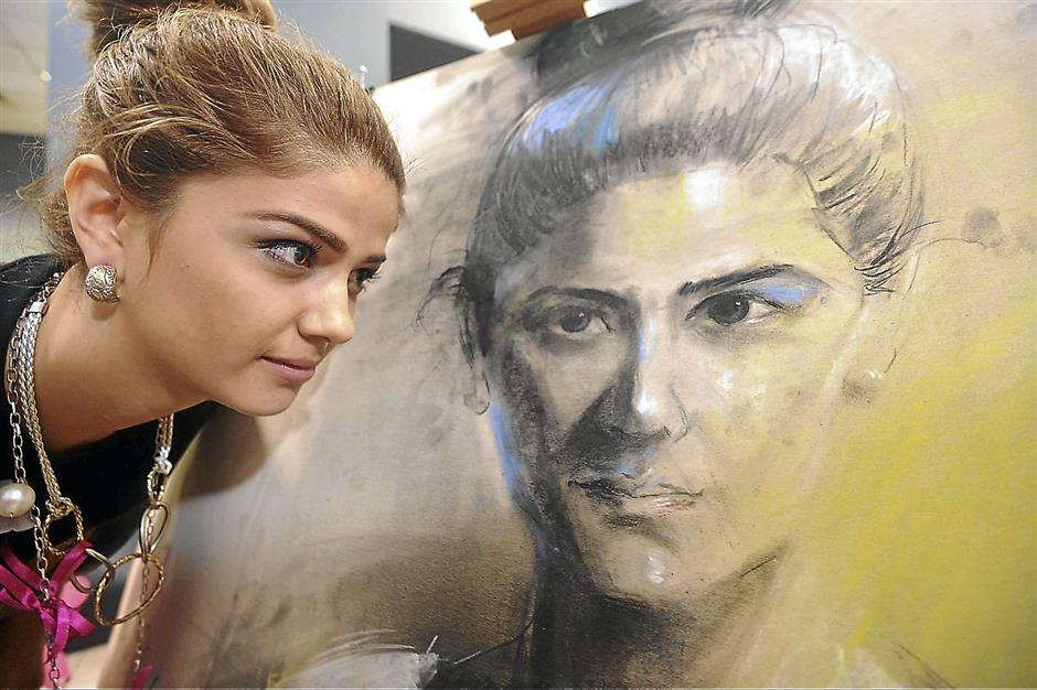 Closer inspection: Miss Tourism Costa Rica Nathalie del Carmen Alvarez Mora takes a close look her portrait.
