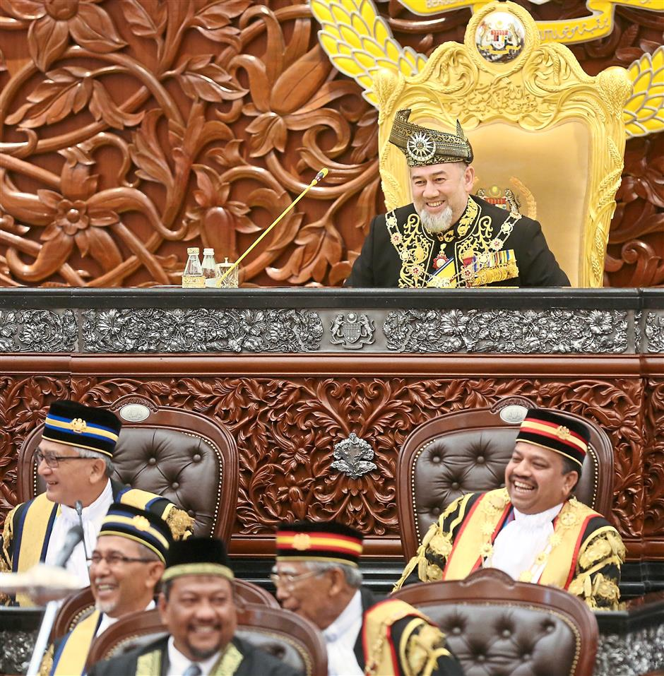Sultan Muhammad V is all smiles after telling the parliamentarians to sit down and don't run away before delivering his Royal Address at the official opening of the first session of the 14th Parliament.
