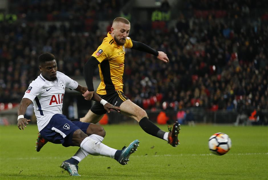 Tottenham\'s Serge Aurier, left takes a shot at goal under pressure from Newport\'s Dan Butler during the English FA Cup fourth round replay soccer match between Tottenham Hotspur and Newport County at Wembley stadium in London, Wednesday, Feb. 7, 2018. (AP Photo/Alastair Grant)
