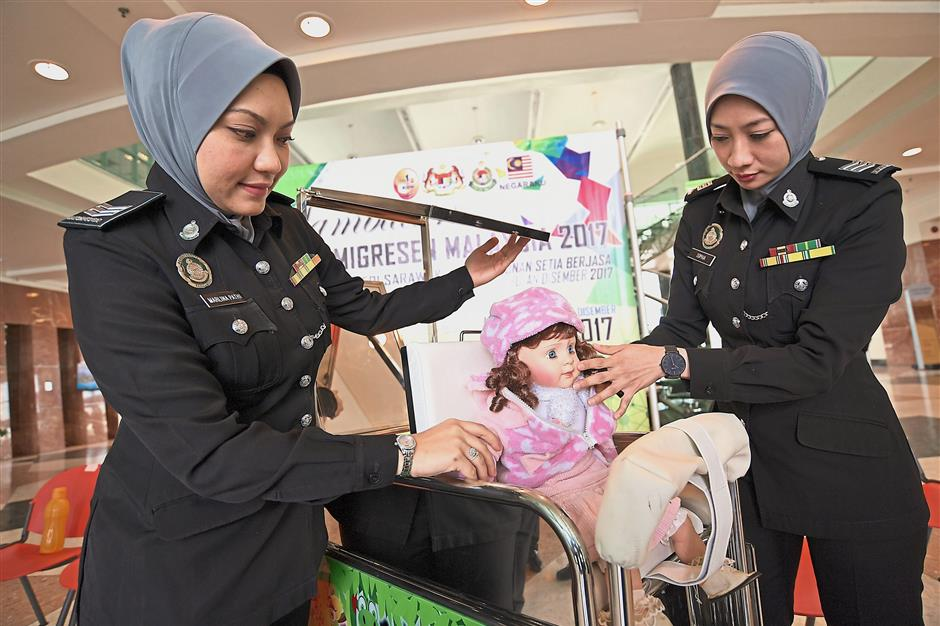 KUCHING, 5 Dis -- Dua kakitangan Jabatan Imigresen Sarawak Marlina Pathi, 33, (kiri) dan Sophia Lee Mohamad, 36, mencuba alat MARS Mirror rekaanJabatan Imigresen Malaysia Sarawak selepas pelancarannya sempena sambutan Hari Imigresen Peringkat Negeri Sarawak 2017 hari ini.Inovasi tersebut yang telah memenangi Kategori Agensi Persekutuan baru-baru ini merupakan penyelesaian masalah ketika mengambil gambar live capture semasa proses permohonan pasport kanak-kanak dua tahun ke bawah.--fotoBERNAMA (2017) HAK CIPTA TERPELIHARA