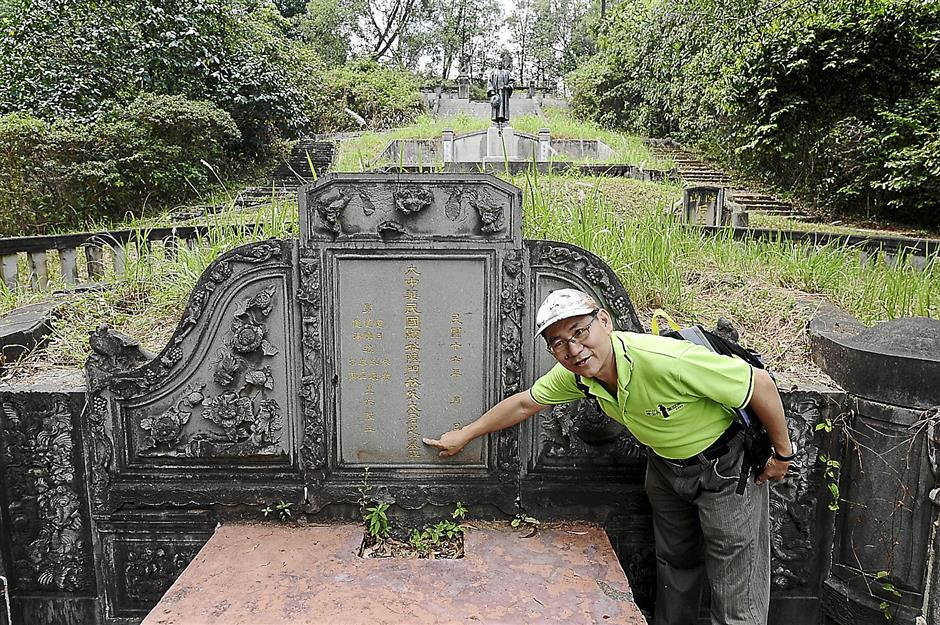 Tracing the history: Kuala Lumpur and Selangor Chinese Assembly Hall chief executive officer Tang Ah Chai explaining the writings on the grave of Loke Yew's wife.