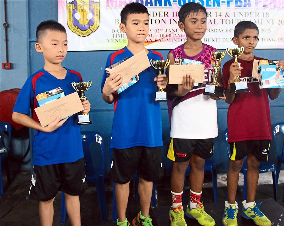 Little champs: (From right) The Boy's Under-10 Doubles winners Tamilarasu and Zul Muis posing with runners-up Ee Wei and Ting Yong with their trophies and prize money. (Right pic) Ting Yong (right) keeps a close watch as his partner Ee Wei executes a service during the game.