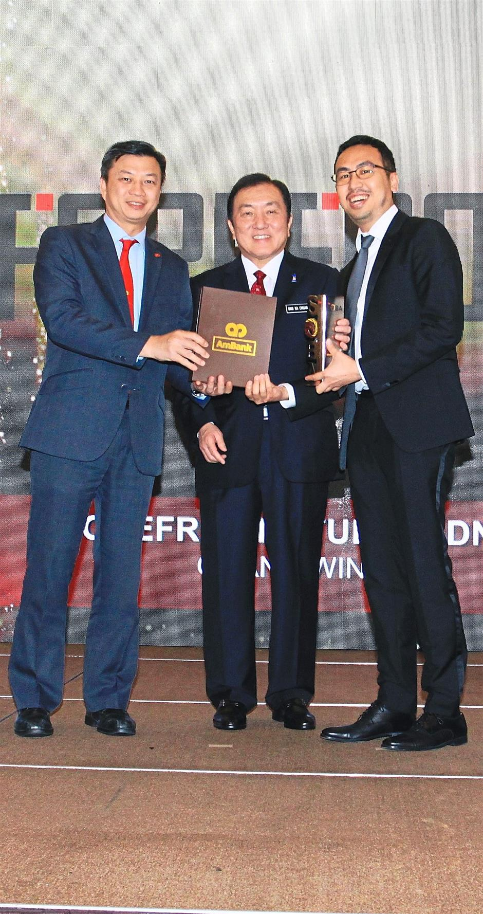 Yap presenting the Platinum award for Malaysian Business of the Year to Forefront Studio Sdn Bhd chief executive officer, Darien Mah while International Trade and Industry Minister II, Datuk Seri Ong Ka Chuan looks on.