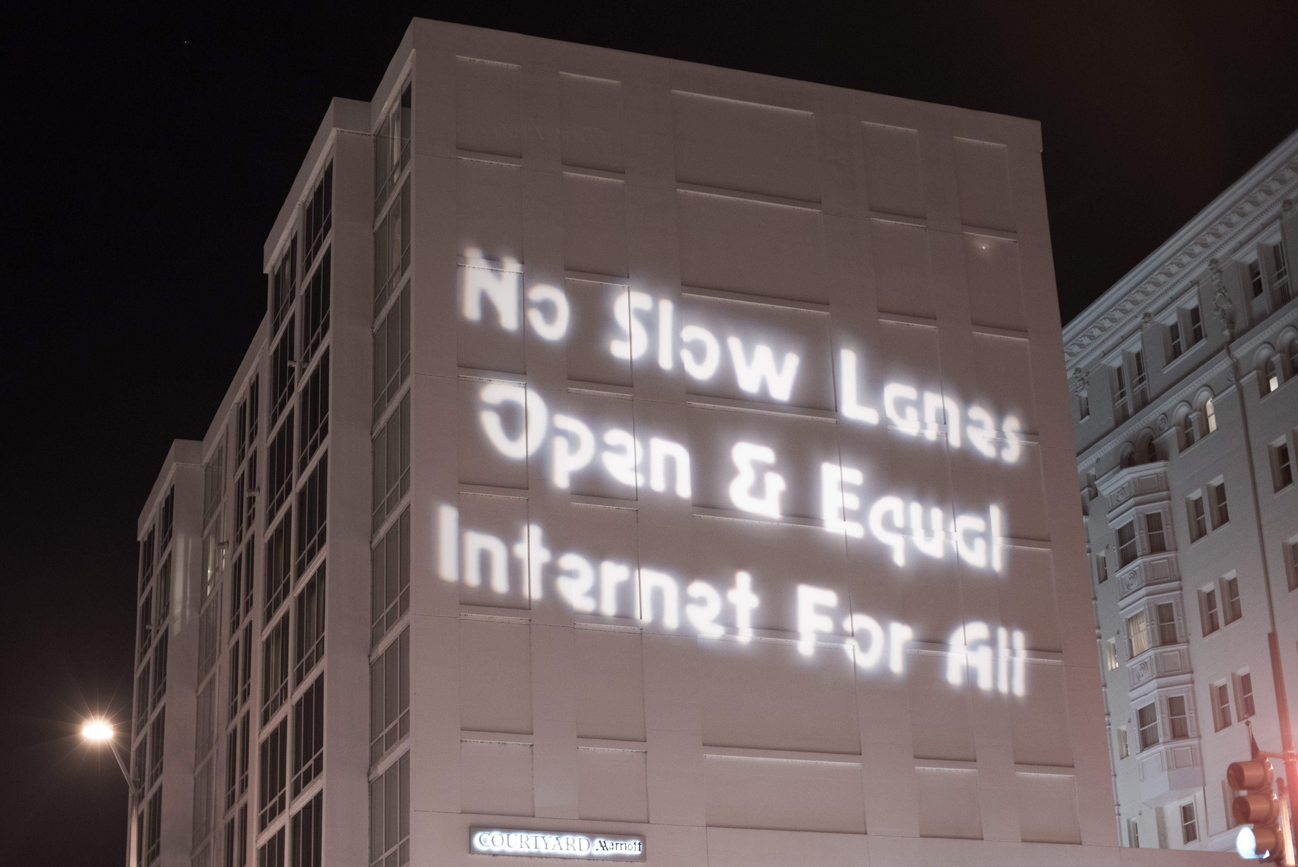 A sign is projected onto a building during a demonstration supporting net neutrality in a protest against a plan by Federal Communications Commission (FCC) head Ajit Pai, on December 7, 2017 in Washington. Demonstrations in support of net neutrality are planned nationwide at hundreds of Verizon stores and other venues. / AFP PHOTO / mari matsuri
