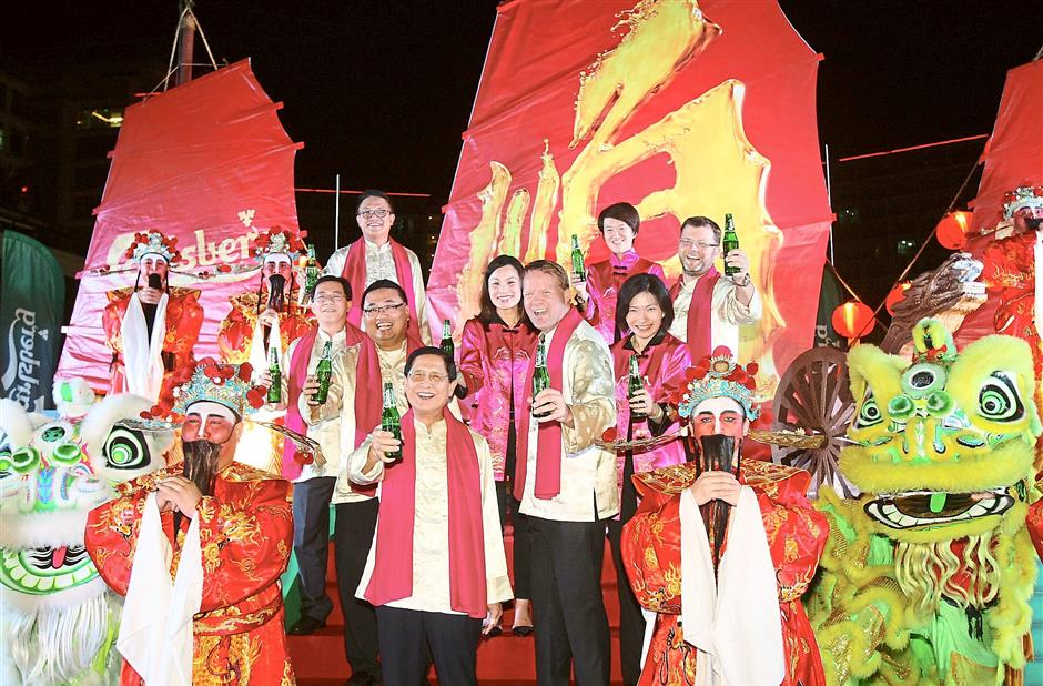 All set: Carlsberg Malaysia senior management staff posing with the Gods of Prosperity and lion dance performers at the launch of its CNY campaign in Oasis Square, Ara Damansara.