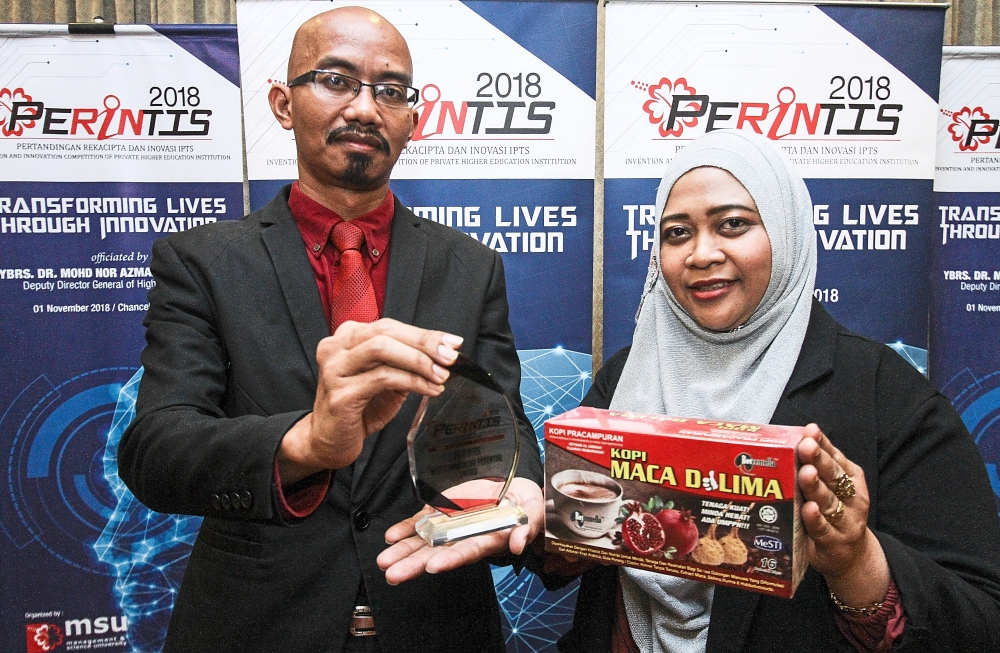 Dr Rosjulila (right) and Dr Zulhabri with their winning product, 'Kopi Maca Delima' instant herbal coffee, which won Best Commercial Potential Award at Perintis 2018.