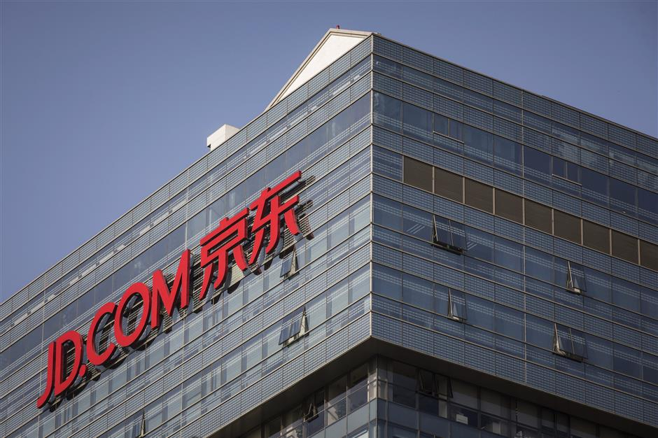 Signage foru00a0JD.com Inc. is displayed atop the company\'s headquarters in Beijing, China, on Monday, Oct. 23, 2017. JD.com isu00a0China\'s second-largest online mall. Photographer: Qilai Shen/Bloomberg