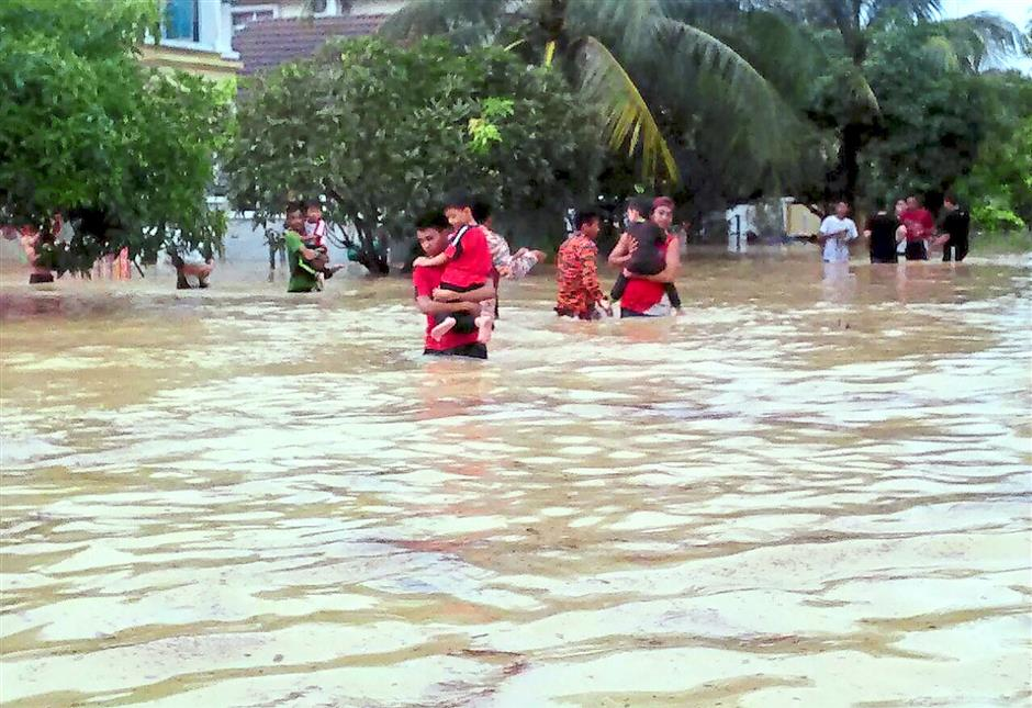 3 Fire and rescue department personnel carrying the kindergarten students in Puncak Alam to safety as waters reached 1m.