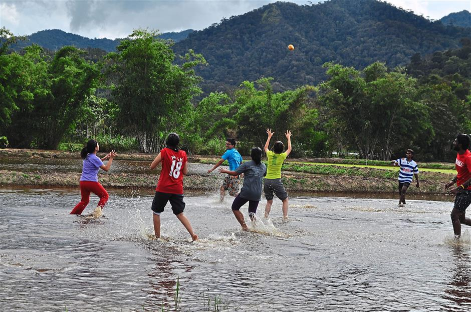 Fun and games: Off-duty Project WHEE participants having a ball of a time playing in the padi fields.