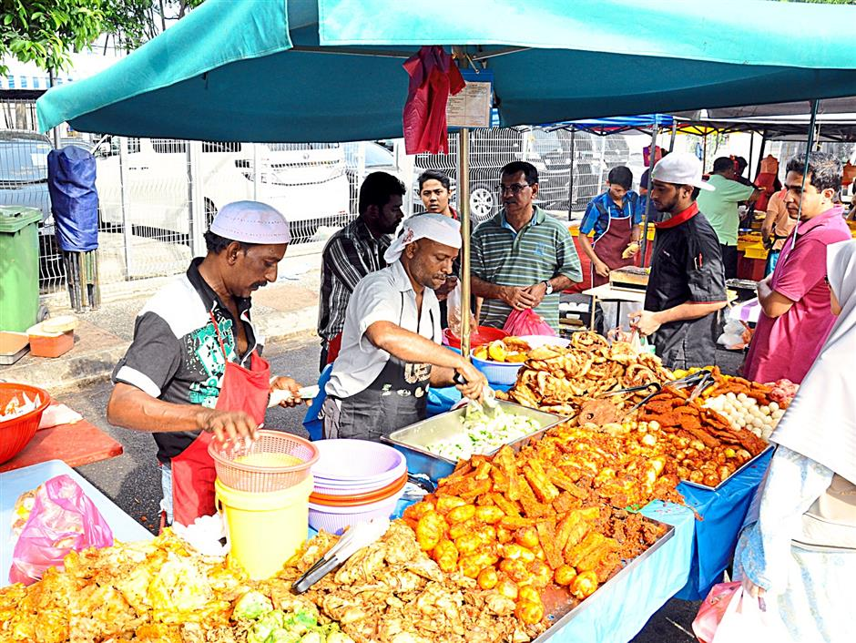 (extreme left) Mohd Nazri Syed Mohd, 55, and Baharuddin Jaafar, 42, moving quickly to pack the combination of ingredients including sotong and prawns and fishball to make pasembur for customers