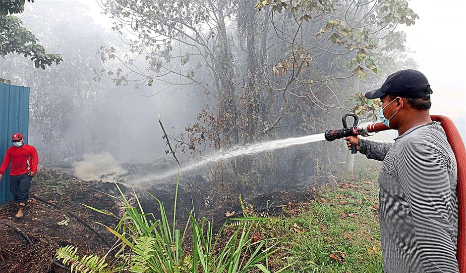 Firemen and Klang Municipal Council enforcement officers putting out the peat fire  near Jalan Sopan off Jalan Johan Setia, Klang yesterday.(13/03/2014/S.S.KANESAN/The Star)