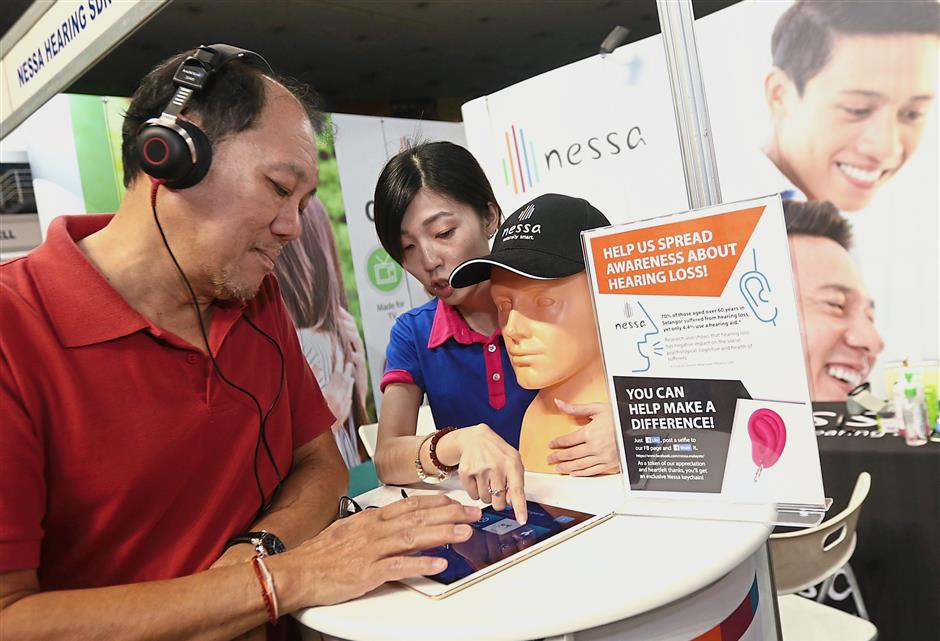 Cheryl (right) showing visitor Quah Seng Sun how to use the hearing aid device at the Nessa Hearing Sdn Bhd booth.