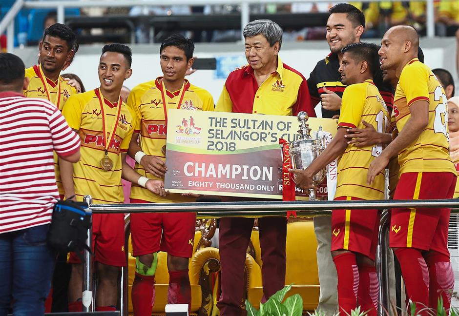 Sultan Sharafuddin (centre) and Tengku Amir Shah (third from right) presenting the trophy and a cheque for RM80,000 to the Selangor Selection after the state side clinched the 17th Sultan of Selangors Cup at Shah Alam Stadium. — Photos by IZZRAFIQ ALIAS, M.AZHAR ARIF and MUHAMAD SHAHRIL ROSLI / The Star.