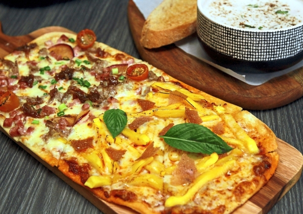 Diners can order a mixed pizza, combining the Duck Confit (left) and Nang Nak Knowhere.