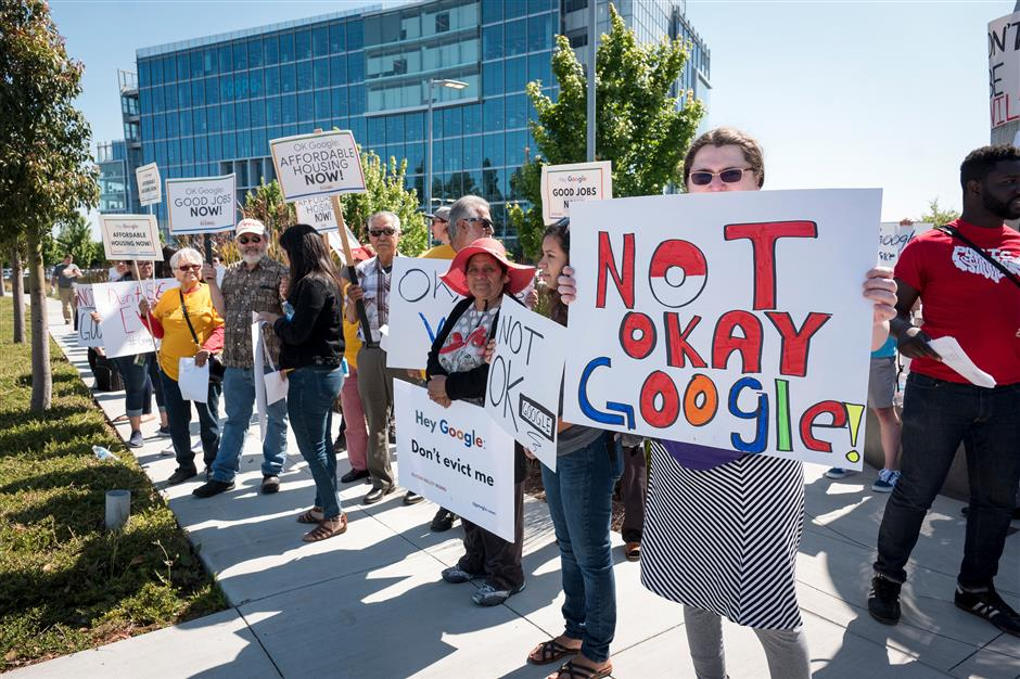 Protesters carry signs while demonstrating outside the Alphabet Inc. annual shareholders meeting in Sunnyvale, California, U.S., on Wednesday, June 19, 2019. Google workers, shareholders and activists used the annual meeting to protest a range of issues, including contractor rights and the tech giant\'s business in China. Photographer: David Paul Morris/Bloomberg