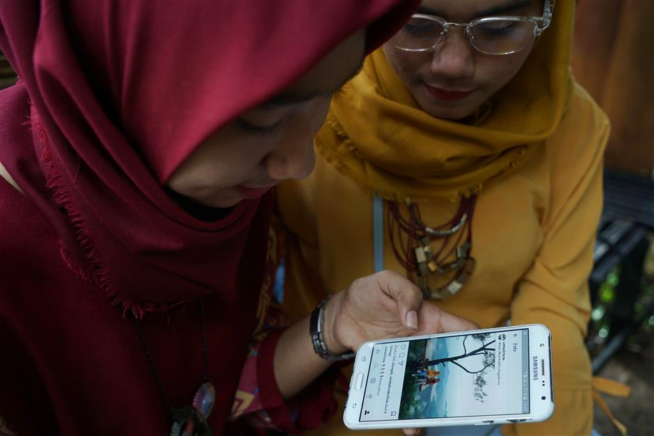 Visitors look at a photograph taken on a platform at the Kalibiru Tourism Village and posted on the Instagram Inc. social media platform in Kulon Progo Regency, Special Region of Yogyakarta, Indonesia, on Saturday, Feb. 3, 2018. In Kalibiru, near Yogyakarta, villagers built treetop platforms to provide a full-fledged destination for social media photo-ops. They installed cameras and hired photographers to advise on the best poses to showcase the background of verdant hills and a shimmering blue reservoir. Photographer: Dimas Ardian/Bloomberg
