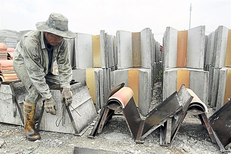 A worker preparing the mould to make the glazed concrete drain.