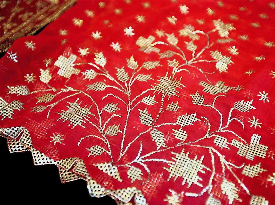 A keringkam scarf with a floral motif embroidered in gold thread. Keringkam, the traditional embroidery of the Sarawak Malays, is handstitched with gold or silver threads.