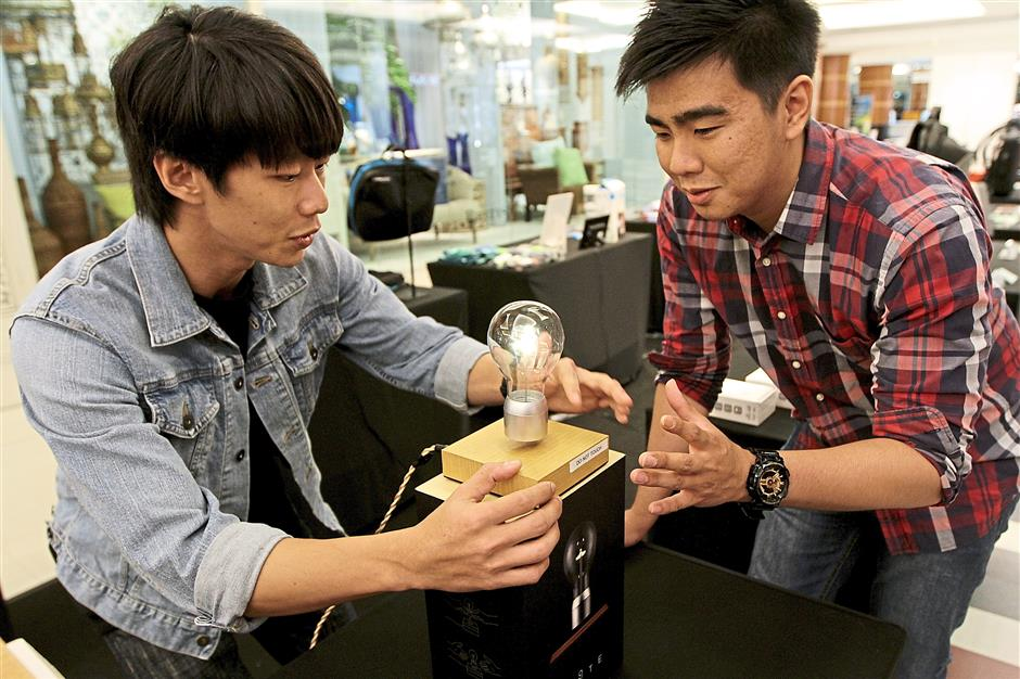 Look ma, no hands – Chan (left) showing off the 'floating light bulb' to a potential customer. — Photos: YAP CHEE HONG/The Star