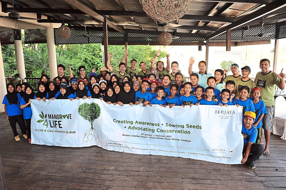 Memento of group effort: Pupils of SK Kuala Teriang in a group photo with members of Malaysian Nature Society and the media.