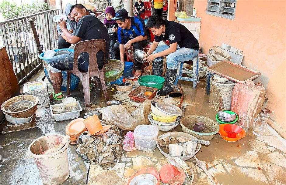Lots of scrubbing to do: A restaurant owner and his family cleaning plates and cooking utensils.
